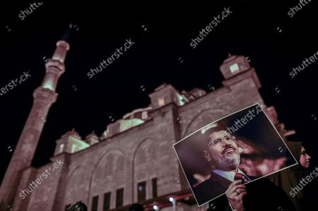 Stock Image of A woman holds a picture of former Egyptian President Mohamed Morsi during a protest for death penalty in Egypt, after the evening pray at Fatih Mosque in Istanbul, Turkey, 10 December 2019.