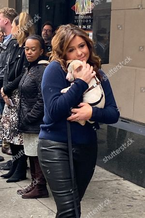 Rachael Ray cuddles with a puppy from the ASPCA while taping a segment