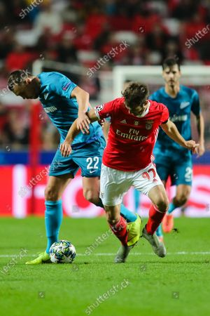 Stock Image of Benfica`s Francisco Ferreira 'Ferro' (R) fights for the ball with Zenit`s Artem Dzyuba during the UEFA Champions League Group G soccer match between Benfica and Zenit St Petersburg held at Luz Stadium, Lisbon, Portugal, 10 December 2019.