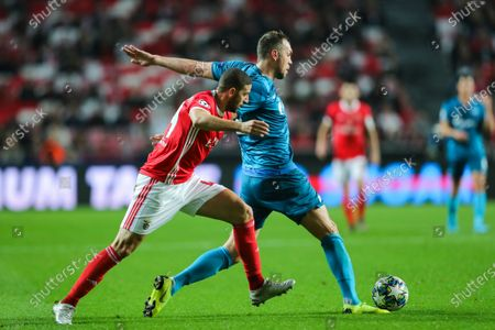Benfica`s Adel Taarabt (L) fights for the ball with Zenit`s Artem Dzyuba during the UEFA Champions League Group G soccer match between Benfica and Zenit St Petersburg held at Luz Stadium, Lisbon, Portugal, 10 December 2019.