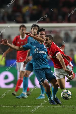 Benfica`s Adel Taarabt (R) fights for the ball with Zenit`s Magomed Ozdoev during the UEFA Champions League Group G soccer match between Benfica and Zenit St Petersburg held at Luz Stadium, Lisbon, Portugal, 10 December 2019.