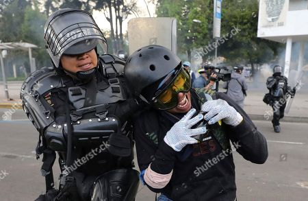 Riot police detain a student who was protesting against the government during a national strike in Bogota, Colombia, . The student was part of a protest who's demands include asking President Ivan Duque to not make changes in the tax, labor and pension laws that are either before the legislature or rumored to be in development