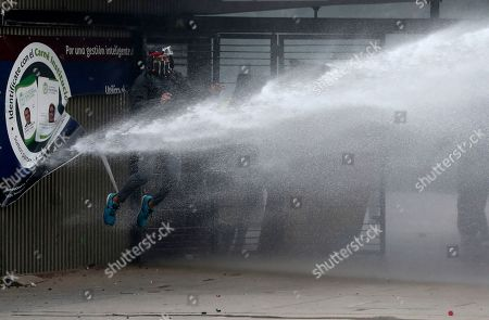 An anti-government demonstrator is sprayed by a police water cannon during a national strike in Bogota, Colombia, . The student was part of a protest who's demands include asking President Ivan Duque to not make changes in the tax, labor and pension laws that are either before the legislature or rumored to be in development