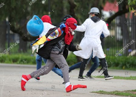 Anti-government students run away from tear gas during a national strike in Bogota, Colombia, . The student was part of a protest who's demands include asking President Ivan Duque to not make changes in the tax, labor and pension laws that are either before the legislature or rumored to be in development