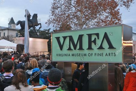 Spectators watch during the unveiling ceremony for a statue titled Rumor's of War by artist Kehinde Wiley at the Virginia Museum of Fine arts in Richmond, Va., . The tarp covering the statue got stuck on the statue during the ceremony