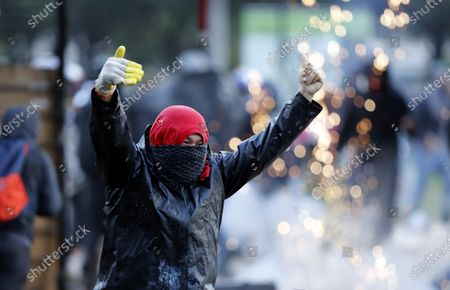 A demonstrator gestures during a clash with members of the ESMAD police squad after a protest against the government of Colombian President Ivan Duque, at the entrance of the National University in Bogota, Colombia, 10 December 2019.