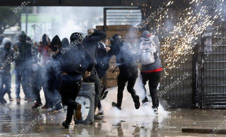 Stock Image of Demonstrators clash with members of the ESMAD police squad after a protest against the government of Colombian President Ivan Duque, at the entrance of the National University in Bogota, Colombia, 10 December 2019.