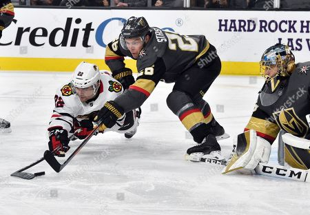 Chicago Blackhawks center Ryan Carpenter (22) and Vegas Golden Knights center Paul Stastny (26) vie for the puck as goaltender Marc-Andre Fleury defends during the third period of an NHL hockey game, in Las Vegas