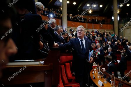 Stock Photo of French High Commissioner for Pension Reform Jean-Paul Delevoye (C) greets people as he arrives before French Prime Minister Edouard Philippe (not pictured) unveils the details of a pension reform plan before the CESE (Economic, Social and Environmental Council), as hundreds of thousands of people demonstrated the day before on the sixth day of a general strike, in Paris, France, 11 December 2019.
