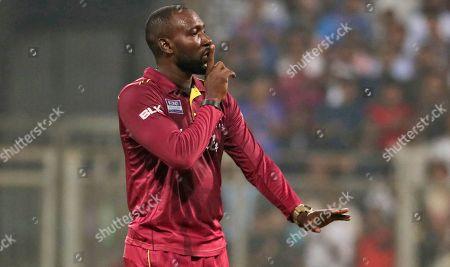 West Indies' Kesrick Williams celebrates the dismissal of India's Rohit Sharma during the third Twenty20 international cricket match between India and West Indies in Mumbai, India