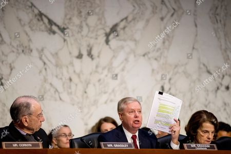 Chuck Grassley, Lindsey Graham, Dianne Feinstein. Chairman Lindsey Graham, R-S.C., center, accompanied by Sen. Chuck Grassley, R-Iowa, left, and Ranking Member Sen. Dianne Feinstein, D-Calif., right, holds up a report while giving an opening statement as Department of Justice Inspector General Michael Horowitz, center foreground, testifies at a Senate Judiciary Committee hearing on the Inspector General's report on alleged abuses of the Foreign Intelligence Surveillance Act, on Capitol Hill in Washington