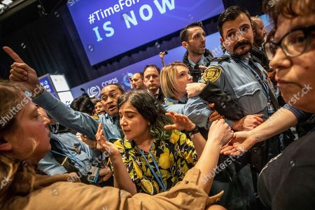 Stock Image of Demonstrators scuffle with UN security staff members during a protest at the COP25 summit in Madrid,. World leaders agreed in Paris four years ago to keep global warming below 2 degrees Celsius (3.6 degrees Fahrenheit), ideally no more than 1.5 C (2.7 F) by the end of the century. Scientists say countries will miss both of those goals by a wide margin unless drastic steps are taken to begin cutting greenhouse gas emissions next year. Claiming that the message doesn't seem to be getting through to governments, over one hundred activists led by representatives of indigenous peoples from Latin and North America made their way to the talks' venue, blocking for some tense minutes the entrance to a plenary meeting where U.N. Secretary General Antonio Guterres was about to speak