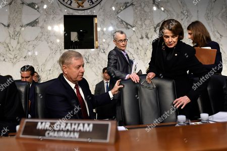 Senate Judiciary Committee Chairman Lindsey Graham, R-S.C., left, helps to move the chair for ranking member, Sen. Dianne Feinstein, D-Calif., right, as they arrive for a hearing with Department of Justice Inspector General Michael Horowitz on Capitol Hill in Washington, to look at the Inspector General's report on alleged abuses of the Foreign Intelligence Surveillance Act
