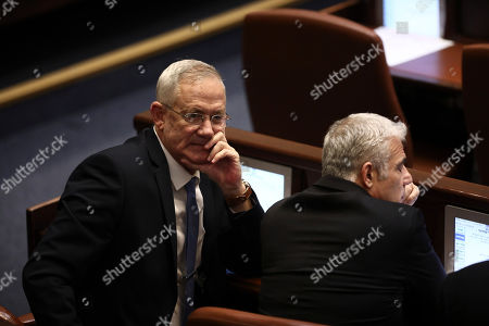 Blue and White party leaders Benny Gantz, left, and Yair Lapid attend a Knesset session in Jerusalem, . The Israeli parliament began voting to dissolve itself on Wednesday and pave the path to an unprecedented third election within a year