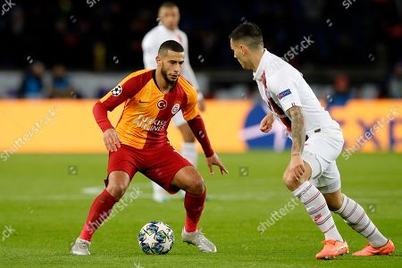 Galatasaray's Younes Belhanda vies for the ball with PSG's Leandro Paredes, right, during the Champions League group A soccer match between PSG and Galatasaray at the Parc des Princes stadium in Paris