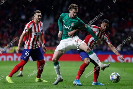 Lokomotiv's Aleksei Miranchuk, centre, vies for the ball with Atletico Madrid's Renan Lodi as Atletico Madrid's Hector Herrera looks on during the Champions League Group D soccer match between Atletico Madrid and Lokomotiv Moscow at Wanda Metropolitano stadium in Madrid, Spain