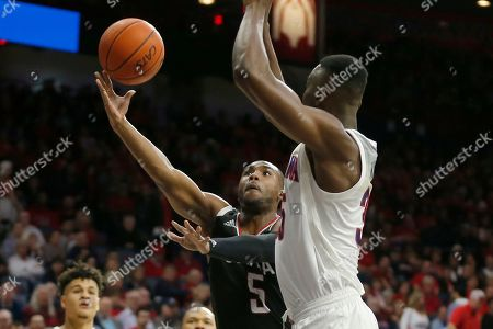 Omaha guard KJ Robinson (5) drives around Arizona center Christian Koloko in the first half during an NCAA college basketball game, in Tucson, Ariz