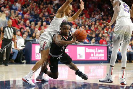 Omaha guard KJ Robinson (5) passes the ball in between Arizona guard Jemarl Baker Jr. and Christian Koloko (35) in the first half during an NCAA college basketball game, in Tucson, Ariz