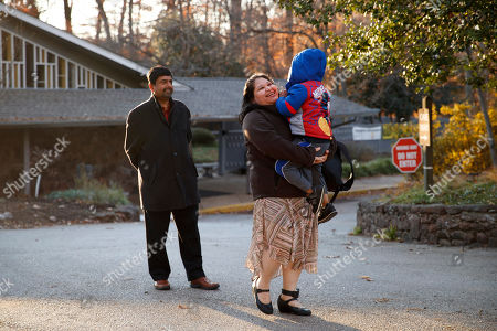 Rosa Gutierrez Lopez, Abhi Janamanchi. Rev. Abhi Janamanchi, left, watches as holds Rosa Gutierrez Lopez picks up her son John, 7, who has Down syndrome, after John arrived on the school bus to Cedar Lane Unitarian Universalist Church where the Gutierrez Lopez family is living, in Bethesda, Md., . Gutierrez Lopez, who a year ago became the first unauthorized immigrant to get refuge inside a religious institution in the Washington area, has now been living in sanctuary for a year due to a deportation order