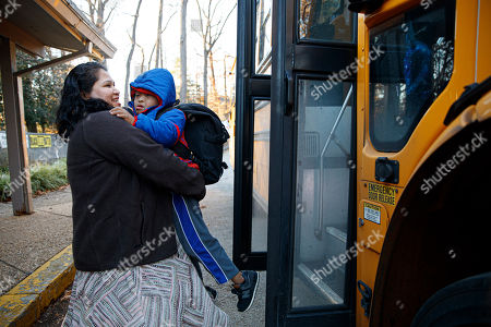Rosa Gutierrez Lopez, from el Salvador, left, greets her son John, 7, who has Down syndrome, as he gets off the school bus at Cedar Lane Unitarian Universalist Church where the family is living in Bethesda, Md., . Gutierrez Lopez, who a year ago became the first unauthorized immigrant to get refuge inside a religious institution in the Washington area has now been living in sanctuary for a year due to a deportation order