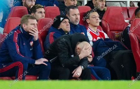 Interim Manager Freddie Ljungberg of Arsenal reacts alongside Per Mertesacker as Mesut Ozil looks on