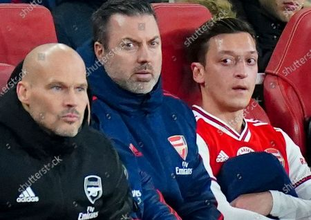 Mesut Ozil of Arsenal looks on near Interim Manager Freddie Ljungberg after being substituted