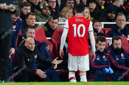 Mesut Ozil of Arsenal appears to ignore the hand of Interim Manager Freddie Ljungberg of Arsenal after being substituted