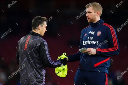 Stock Photo of Mesut Ozil of Arsenal with coach Per Mertesacker