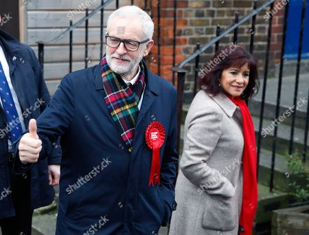 British opposition Labour Party leader Jeremy Corbyn, left and his wife Laura Alvarez leave after voting in the general election in Islington, London, England, .U.K. voters are deciding Thursday who they want to resolve the stalemate over Brexit in a parliamentary election widely seen as one of the most decisive in modern times