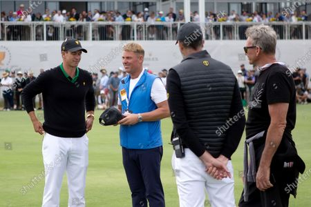 Adam Scott of Australia chats with former Australian test cricketer Shane Warne during round 2 of The Presidents Cup