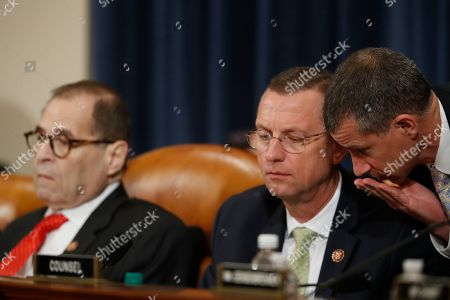 House Judiciary Committee ranking member Rep. Doug Collins, R-Ga., center, talks to Republican staff attorney Steve Castor, right, during a House Judiciary Committee markup of the articles of impeachment against President Donald Trump, on Capitol Hill in Washington. House Judiciary Committee Chairman Rep. Jerrold Nadler, D-N.Y., is left