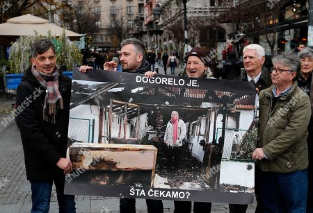 """Members of the Independent Journalists' Association hold a poster shows a journalist Milan Jovanovic in his burned house that reads: """"What are we waiting for?"""" during a protest in Belgrade, Serbia, . The protest marked a year since assailants set fire to the house of a journalist outside Belgrade. Milan Jovanovic escaped the fire that burned the house to the ground"""