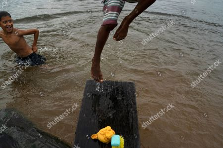 Stock Picture of 10-year-old Kevin performs a somersault in the Uruara river as his friend looks, at the entrance of the Renascer conservative unit of the Amazon rainforest in Prainha, Para state, Brazil. The clock is ticking. Already the Amazon is growing warmer and drier, losing its capacity to recycle water, and may become savannah in 15 to 30 years, said Carlos Nobre, a climate scientist at the University of Sao Paulo