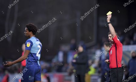 Sido Jombati of Wycombe Wanderers is shown a yellow card by Neil Hair match referee