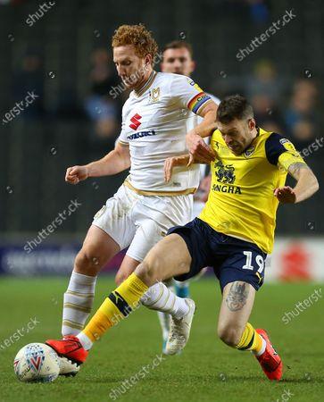 Jamie Mackie of Oxford United battles with Dean Lewington of Milton Keynes Dons