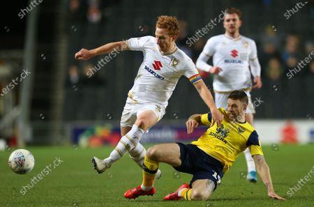 Dean Lewington of Milton Keynes Dons is tackled by  Jamie Mackie of Oxford United