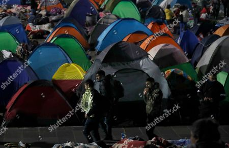 Pilgrims walk past a tent city outside the Basilica of Guadalupe in Mexico City, . Officials estimated a crowd of 9.8 million in the area surrounding one of the Roman Catholic world's holiest shrines, according to national civil defense coordinator David Leon. If so, that would exceed the population of Mexico City itself