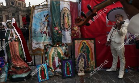 Stock Picture of Mexican Charro musicians play next to an improvised altar outside the Basilica of Guadalupe in Mexico City, . Officials estimated a crowd of 9.8 million in the area surrounding one of the Roman Catholic world's holiest shrines, according to national civil defense coordinator David Leon. If so, that would exceed the population of Mexico City itself