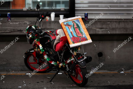 A motorcycle wit an icon of the Virgin of Guadalupe is parked near the Basilica of Guadalupe in Mexico City, . Officials estimated a crowd of 9.8 million in the area surrounding one of the Roman Catholic world's holiest shrines, according to national civil defense coordinator David Leon. If so, that would exceed the population of Mexico City itself