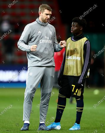 Arsenal Interim Assistant Manager Per Mertesacker speaks to Bukayo Saka of Arsenal.