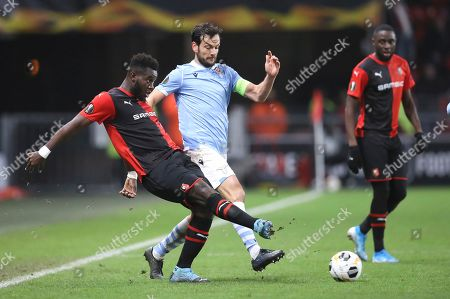 Rennes' M'Baye Niang, left, kicks the ball ahead of Lazio's Marco Parolo during the Europa League Group E soccer match between Rennes and Lazio, at the Roazhon Park stadium in Rennes, France