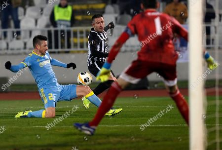 Astana's Antonio Rukavina, left, tries to block a shot from Partizan's Zoran Tosic, center, during the Europa League group L soccer match between Partizan Belgrade and Astana at the Partizan stadium in Belgrade, Serbia