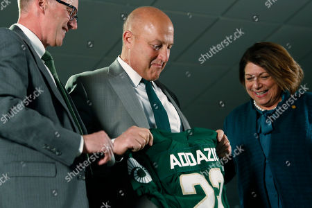 Stock Image of R m. Steve Addazio, center, looks down at a jersey presented to him by athletic director Joe Parker, left, and President Joyce McConnell during an announcement that Addazio has been hired as the new head football coach at Colorado State University at a news conference at the school, in Fort Collins, Colo