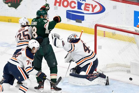 Minnesota Wild's Jordan Greenway, center, puts the puck past Edmonton Oilers goalie Mike Smith, right, for a goal in the first period of an NHL hockey game, Thursday, Dec.12, 2019, in St. Paul, Minn