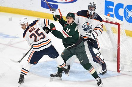 Edmonton Oilers goalie Mike Smith, right, looks over teammate Darnell Nurse (25) and Minnesota Wild's Joel Eriksson Ek, center, of Sweden, for the puck in the first period of an NHL hockey game, Thursday, Dec.12, 2019, in St. Paul, Minn