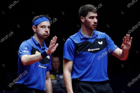 Timo Boll (L) and Patrick Franziska (R) of Germany react as they play against Liao Cheng-Ting and Lin Yun-Ju of Chinese Taipei (not pictured) during Men's Doubles semifinals match of the ITTF World Tour Grand Finals Table Tennis tournament in Zhengzhou, China, 13 December 2019.