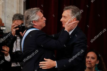 Argentina's new President Alberto Fernandez, left, embraces outgoing president Mauricio Macri after taking the oath of office at the Congress in Buenos Aires, Argentina