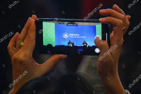 A woman records a video as former US president Barack Obama (L) and his sister Maya Soetoro-ng (R) talk on stage at an Obama Foundation event in Kuala Lumpur, Malaysia, 13 December 2019. Obama and his wife Michelle are in Kuala Lumpur for the inaugural Leaders: Asia-Pacific conference, focused on promoting women's education in the region.