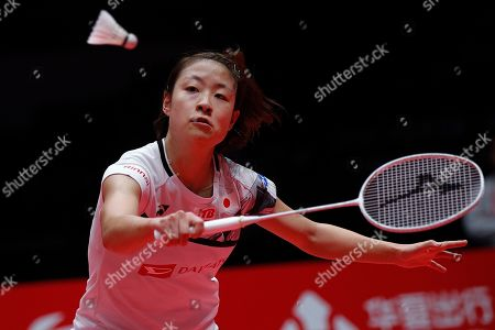 Japan's Nozomi Okuhara hits a return shot against Thailand's Ratchanok Intanon during their women's singles badminton match at the World Tour Finals in Guangzhou in south China's Guangdong province