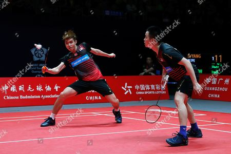 Soh Wooi Yik, Aaron Chia. Malaysia's Soh Wooi Yik, left, hits a return shot next to his teammate Aaron Chia during their men's doubles badminton match against Taiwan's Lu Ching Yao and Yang Po Han at the World Tour Finals in Guangzhou in south China's Guangdong province